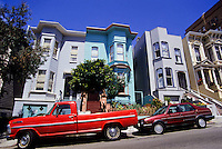Old colorfull painted wooden victorian style houses and red cars in San Francisco, California, USA