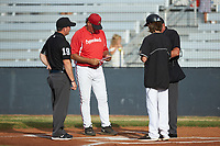 The head coach of the Lake Norman Copperheads meets with Mooresville Spinners head coach Tripp Hamrick (right) and umpires Gary Keller (left) and Britt Kennerly (right) prior to their Southern Collegiate Baseball League game at Moor Park on July 6, 2020 in Mooresville, NC.  The Spinners defeated the Copperheads 3-2. (Brian Westerholt/Four Seam Images)