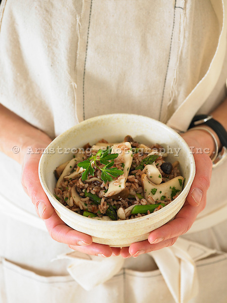A woman's hands holding a bowl of pink rice pilaf with wild mushrooms, asparagus, and parsley.