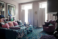 In the spacious reception area, an L-shaped sofa upholstered in a bold floral fabric, and a geometrically patterned carpet create a bold contrast to the pale pink walls