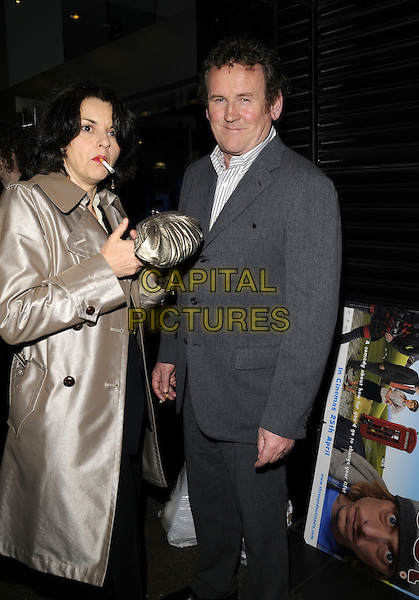"INES & COLM MEANY. World Premiere of ""Three and Out"" at the Odeon Leicester Square, London, England..April 21st 2008 .3 full length grey gray suit married husband wife lighting cigarette smoking gold clutch bag purse .CAP/CAN.©Can Nguyen/Capital Pictures."