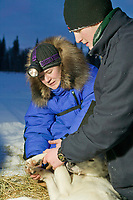 Veterinarian Margaret Terhar and 14 year old musher Daniel Joinson from Dawson City, YT, examine the injured foot of a dog at Twin Bears rest stop, during the 120 mile 2004 Junior Yukon Quest in Fairbanks, Alaska