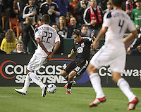 Josh Wolfe (16) of D.C. United shoots the ball between Leonardo (22) and Omar Gonzalez (4) of the Los Angeles Galaxy during an MLS match at RFK Stadium, on April 9 2011, in Washington D.C.The game ended in a 1-1 tie.