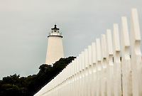 A white picket fence leading to the popular Ocracoke Lighthouse adds to the island's romantic feel. Ocracoke Light remains among the oldest lighthouses still active on the southern coast of North Carolina's Outer Banks, and it is the second oldest operating lighthouse in the United States (the first is Sandy Hook Light house in New Jersey). The first Ocracoke Lighthouse was built in 1803 on Shell Castle Island inside the Ocracoke Inlet not far from Blackbeard's hideout. Destroyed by lightning in 1818 it was replaced by the current light in 1823 on the banks of the inlet near Ocracoke Village. The white-brick conical lighthouse stands 75 feet tall and has 220 stairs to its top, though visitors are not allowed to climb. Ocracoke Island can only be reached by ferry. Charlotte NC photographer Patrick Schneider has extensive photo collections of the following lighthouses: Bodie Island Lighthouse, Bald Head Island Lighthouse, Cape Fear Lighthouse, Cape Hatteras Lighthouse, Cape Lookout Lighthouse, Currituck Beach Lighthouse, Diamond Shoal Lighthouse, Federal Point Lighthouse, Oak Island Lighthouse, and Ocracoke Lighthouse on Ocracoke Island.