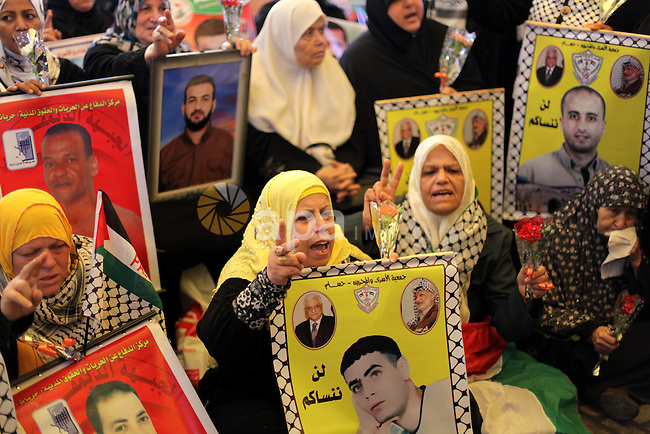 Palestinian women hold pictures of prisoners held in Israeli jails during a protest in front of the Red Cross offices in Gaza city, on Apr. 15, 2013 in solidarity with Palestinian prisoners held by Israel to demand their release from detention without trial. Photo by Ashraf Amra
