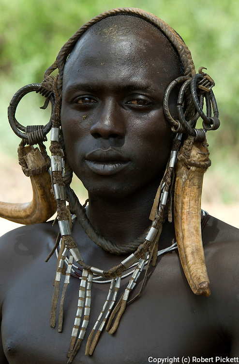 Young Man wearing head gear, Mursi Tribe, Mago National Park, Lower Omo Valley, Ethiopia, portrait, person, one, tribes, tribal, indigenous, peoples, Southern, ethnic, rural, local, traditional, culture, primitive,.Africa....
