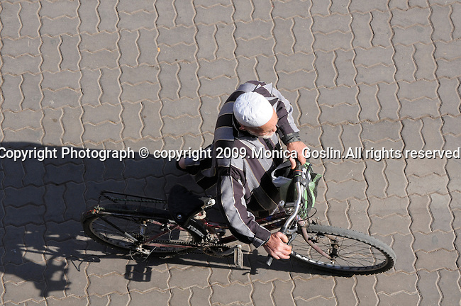 A man on a bike in the busy market place in Marrakesh, Morocco.