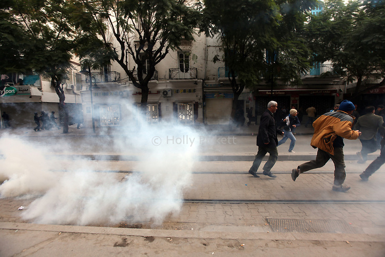 Protesters ran from tear gas during demonstrations in downtown Tunis, Tunisia, Jan. 18, 2011. The Tunisian police and army struggled to maintain order in the capital, as thousands of protesters once again filled the streets.