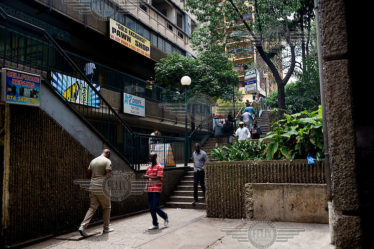 People walk a stairway, past a pawn shop, towards the entrance to the only shopping centre in Hillbrow. The district, in downtown Johannesburg, is the city's most notorious. It is overcrowded, ridden with illegal squats and suffers from high levels of crime much of which is related the thriving illicit drug trade.