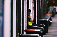 A police officers stands in the doorway of a house believed to be the one where people were arrested in West Street, Newport