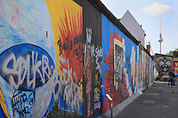 Section of the Berlin Wall, part of the East Side Gallery, a 1.3km long section of the Wall on Muhlenstrasse painted in 1990 on its Eastern side by 105 artists from around the world, Berlin, Germany. Many of the artworks are now damaged by graffiti. In the background is the Fernsehturm or TV Tower near Alexanderplatz. Picture by Manuel Cohen