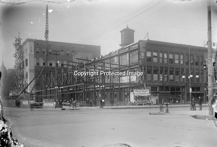 CONSTRUCTION OF MILLER AND PAINE DEPARTMENT STORE, 1914. When the department store decided to replace its rented quarters at Thirteenth and O Streets with a new building, the property owner offered a 99-year lease to the ground but would not sell the site outright. The store cautiously built only two stories on the leased ground. Two years later in 1916, the company added eight stories on the next lot to the west, which it was able to purchase. Both structures were designed by the Lincoln architects Berlinghof and Davis, using buff brick and gleaming white terra-cotta trim. A sidewalk vendor is offering fresh fruits in front of the construction site.<br /> <br /> Photographs taken on black and white glass negatives by African American photographer(s) John Johnson and Earl McWilliams from 1910 to 1925 in Lincoln, Nebraska. Douglas Keister has 280 5x7 glass negatives taken by these photographers. Larger scans available on request.
