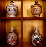 In the dining room a collection of ceramic and glass vases is displayed on gilded open shelving