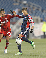 New England Revolution defender Chris Tierney (8) takes a shot as Toronto FC midfielder Matias Laba (20) closes. In a Major League Soccer (MLS) match, the New England Revolution (blue) defeated Toronto FC (red), 2-0, at Gillette Stadium on May 25, 2013.