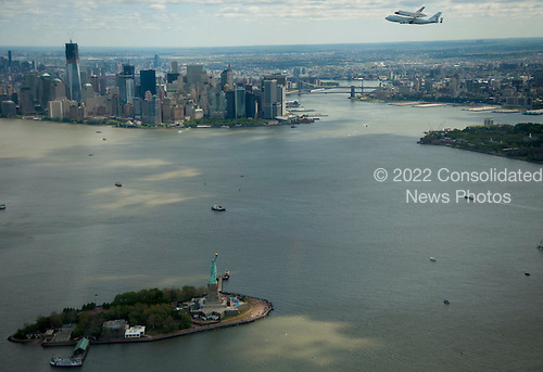 Space shuttle Enterprise, mounted atop a NASA 747 Shuttle Carrier Aircraft (SCA), is seen as it flies near the Statue of Liberty and the Manhattan skyline, Friday, April 27, 2012, in New York. Enterprise was the first shuttle orbiter built for NASA performing test flights in the atmosphere and was incapable of spaceflight. Originally housed at the Smithsonian's Steven F. Udvar-Hazy Center, Enterprise will be demated from the SCA and placed on a barge that will eventually be moved by tugboat up the Hudson River to the Intrepid Sea, Air & Space Museum in June. Photo Credit: (NASA/Robert Markowitz).Mandatory Credit: Robert Markowitz / NASA via CNP
