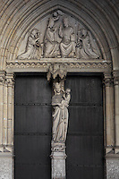 General view of entrance to the lower chapel with coronation of the virgin in the tympanum and Virgin and Child sculpture decorating the trumeau, La Sainte-Chapelle (The Holy Chapel), 1248, Paris, France. La Sainte-Chapelle was commissioned by King Louis IX to house his collection of Passion Relics, including the Crown of Thorns. The Sainte-Chapelle is considered among the highest achievements of the Rayonnant period of Gothic architecture. Picture by Manuel Cohen