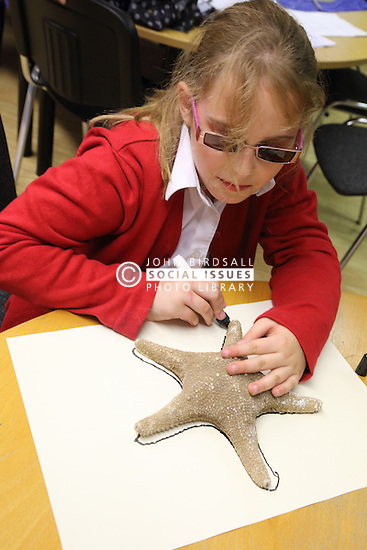 Visually impaired girl drawing round large shell. Mysight Nottingham