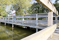 NWA Democrat-Gazette/DAVID GOTTSCHALK  David Powell, of Springdale, casts a line from the docks Tuesday, September 15, 2015 at Lake Fayetteville. Powell, fishing for bass, alternates between Lake Elmdale in Springdale and Lake Fayetteville. Powell said he prefers to fish in the shadows of the docks once the sun rises.