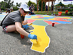 Meara Lindley, a senior trust officer with Edward Jones, puts finishing touches on the state of Florida, part of a gigantic map of the USA that she and co-workers painted on thel playground at Highland Elementary School. Volunteers from the Pacific Life Foundation, Edward Jones, the Riverview Gardens School District, the Boys & Girls Clubs of Greater St. Louis and the community joined KaBOOM! and transformed an empty site into a kid-designed, state-of-the-art playground at Highland Elementary School on Saturday August 18, 2018. The playground - designed from students' drawings - will give more than 400 kids a safe place to play. KaBOOM! is a national non-profit dedicated to bringing balanced and active play into the daily lives of all kids.  Photo by Tim Vizer
