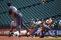 Georgia Tech Yellow Jackets relief pitcher Jared Datoc (28) makes a pickoff throw to first baseman Coleman Poje (16) as Romy Gonzalez (10) of the Miami Hurricanes dives back to the base during game one of the 2017 ACC Baseball Championship at Louisville Slugger Field on May 23, 2017 in Louisville, Kentucky. The Hurricanes walked-off the Yellow Jackets 6-5 in 13 innings. (Brian Westerholt/Four Seam Images)