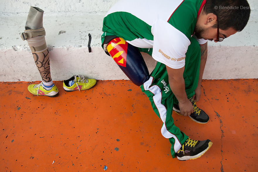 """Jose Luis Almaraz Mendoza, 32, a player from Guerreros Aztecas, removes his prosthetic leg and gets changed before training with his team in Mexico City, Mexico on July 24, 2014. Jose Luis was washing the windows of his home when he fell 3 meters and lost his right leg. Guerreros Aztecas (""""Aztec Warriors"""") is Mexico City's first amputee football team. Founded in July 2013 by five volunteers, they now have 23 players, seven of them have made the national team's shortlist to represent Mexico at this year's Amputee Soccer World Cup in Sinaloathis December.The team trains twice a week for weekend games with other teams. No prostheses are used, so field players missing a lower extremity can only play using crutches. Those missing an upper extremity play as goalkeepers. The teams play six per side with unlimited substitutions. Each half lasts 25 minutes. The causes of the amputations range from accidents to medical interventions – none of which have stopped the Guerreros Aztecas from continuing to play. The players' age, backgrounds and professions cover the full sweep of Mexican society, and they are united by the will to keep their heads held high in a country where discrimination against the disabled remains widespread.(Photo byBénédicte Desrus)"""