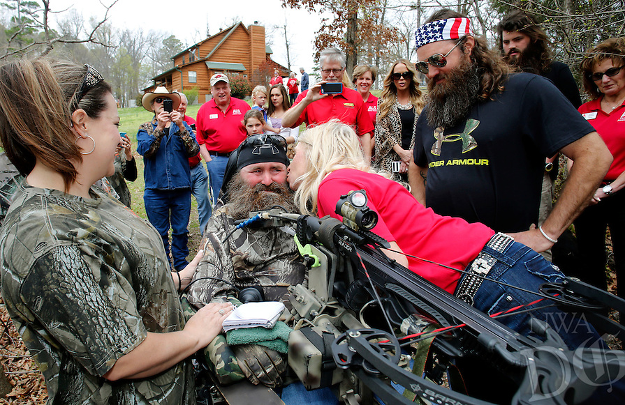 NWA Democrat-Gazette/DAVID GOTTSCHALK - 4/7/15 - Jennifer Necessary, executive director of ALS Arkansas Chapter, leans in to kiss Steve Swope, 44, who was diagnosed in 2008 Amyotrophic Lateral Sclerosis, Tuesday April 7, 2015, as Willie Robertson (right), with the Duck Dynasty franchise watches. Robertson made a surprise appearance as part of the ALS Arkansas Chapter Dream to Reality program.