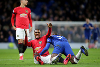 Manchester United recent signing, Odion Ighalo smiles at the assistant referee after being pinned to the ground by Chelsea's Antonio Rudiger during Chelsea vs Manchester United, Premier League Football at Stamford Bridge on 17th February 2020