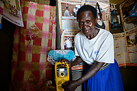UGANDA, Arua, village Ajia, woman Mary Olero with yellow freeplay Radio