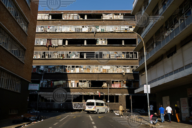 'A fire-damaged' hijacked building' (slang describing illegally occupied squat) in downtown Johannesburg. After a steep decline in the 1990s, the inner city is now a peculiar mix of interspersed working class, down-and-out and gentrified realities, all within a few minutes walk of each other.