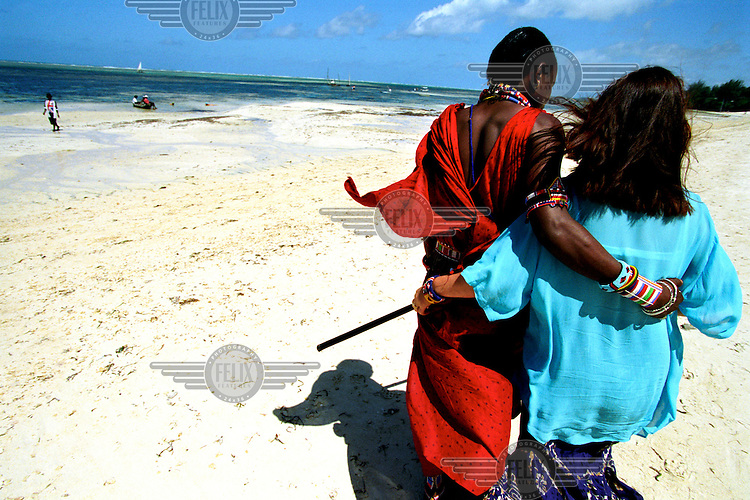 ©Sven Torfinn/Panos Pictures..Kenya, Mombasa, July 2002.on the beach, Masai man (Musa) in traditional clothes together with his German girlfriend (Brigitta from Munich), arm in arm.the beaches around Mombasa are well known to tourists from Europe, not only for their ordinary touristic aspects (sand, sun, sea ...) but also to pick up / encounter local boyfriends / girlfriends, sometimes for one night, sometimes for money and sometimes in the hope to make it to Europe one day
