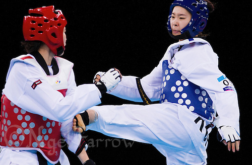 04 DEC 2011 - LONDON, GBR - Hye-Mi Park (KOR) (in blue, on right) battles with Injong Lee (KOR) (in red, on left) during their women's +67kg category quarter final  round contest at the London International Taekwondo Invitational and 2012 Olympic Games test event at the ExCel Exhibition Centre in London, Great Britain .(PHOTO (C) NIGEL FARROW)