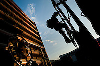 """A young immigrant, heading from El Salvador to the United States, climbs up the cargo train called 'El Tren de la Muerte' (Train of Death) on a train station in Arriaga, Mexico, 25 May 2010. Between 2010 and 2015, the US and Mexico have apprehended almost 1 million illegal immigrants from El Salvador, Honduras, and Guatemala. While the economic reasons remain the most frequent motivation for people from Central America to illegally immigrate to the US, thousands of Salvadorans, Guatemalans, and Hondurans, many of them minors, seek asylum in the US due to the thriving crime and gang-related violence in their region (known as the Northern Triangle). Taking an exhausting and risky journey, riding thousands of miles atop the cargo trains, facing a physical danger and extortion from the organized crime groups that control migrant routes, the """"undocumented"""" still flee to the US, looking for their American dream."""