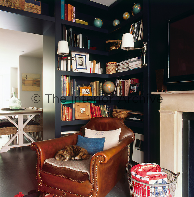 A brown leather armchair stands in the corner of the living room where behind it, books and other objects are arranged on the built-in shelves. An open doorway gives a view through to the dining room