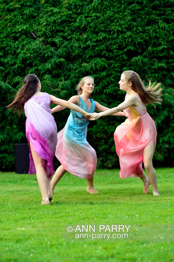 Old Westbury, New York, U.S. 22nd June 2013. Dancers in Lori Belilove &amp; The Isadora Duncan Dance Company, whirl in a circle during a dance of the Three Graces, at the Midsummer Night event at Old Westbury Gardens, throughout the illuminated grounds of the historic Long Island Gold Coast estate.<br /> The Three Graces, or Three Charities, of Greek mythology were Aglaia, Euphrosyne, and Thalia - goddesses of beauty, joy, harmony, pleasure, grace, festivity, adornment, dance, and song. Daughters of Zeus and sea-nymph Eurynome, they were also the attendants, or handmaidens, of Aphrodite and Hera and protectors of vegetation.