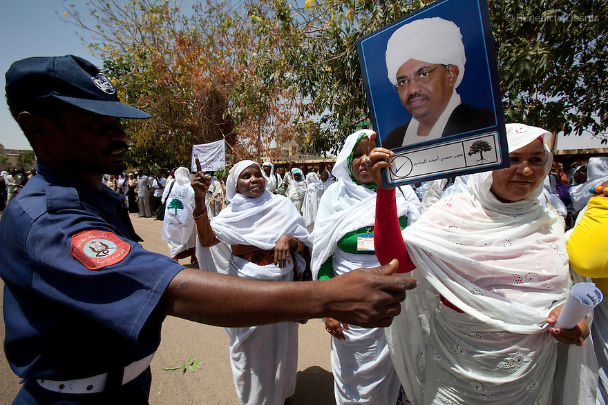 28 april 2010 - Karthoum, Sudan - Supporters of Sudan's President Omar Hassan al-Bashir hold his pictures during a rally at the Ministry of the Council of Ministers in Khartoum. Sudan's president Omar al-Bashir won another term in office on Monday, according to election officials, with a comfortable majority (68 percent of the vote ) in elections marred by boycotts and fraud allegations, becoming the first leader to be elected while facing an international arrest warrant for alleged crimes he orchestrated in the western region of Darfur. The elections take place as Sudan heads toward a referendum in eight months that could lead South Sudan to split off and become Africa's newest nation. Photo credit: Benedicte Desrus
