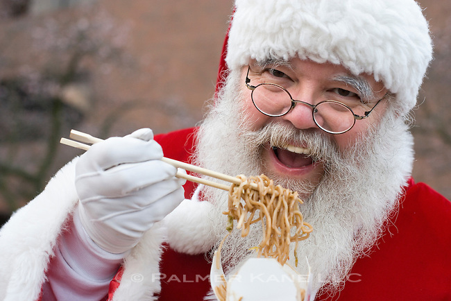 Santa using chopsticks to eat his Chinese Lo Mein noodle meal