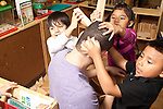Education preschool 3-4 year olds children playing in block area imaginary play barber shop hairdressing young male teacher as the subject children using blocks as hair dressing implements