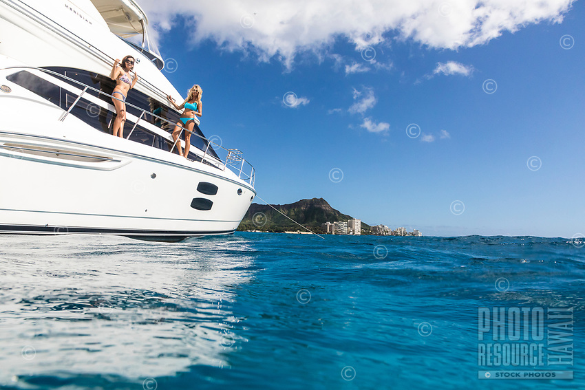 Women enjoy the day on a power cruiser off of Waikiki, O'ahu, with Diamond Head in the distance.