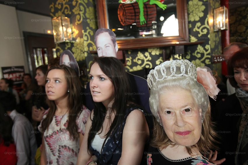 Sarah and Jane watch the wedding celebrations nearby a cardboard cut-out of Prince William and Catherine in the pub decor..Many nationalities, especially English, Australians and French, coming together at midday in the English traditional style 'Frog and Rosbif' Pub in the centre of Paris, to watch the Royal Wedding of Prince William and Catherine Middleton in London. At 119 rue Saint Denis, Paris, France