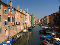 Clean laundry hangs from clotheslines outside windows of apartments above fishing boats moored along Vena canal in Chioggia Ital