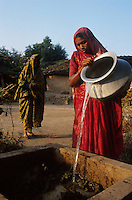 jbo11516 Asia India development climate renewable Energy power decentralized  renewables agriculture gobergas biogas plant for cooking in a village to replace firewoods woman put biomass cow dung and water.Asien Indien Dorf erneuerbare Energie nachhaltigkeit entwicklung Frau gibt Biomasse Kuhdung und wasser in Biogasanlage Biogas zum Kochen Biogas anstatt Feuerholz.copyright Joerg Boethling / agenda