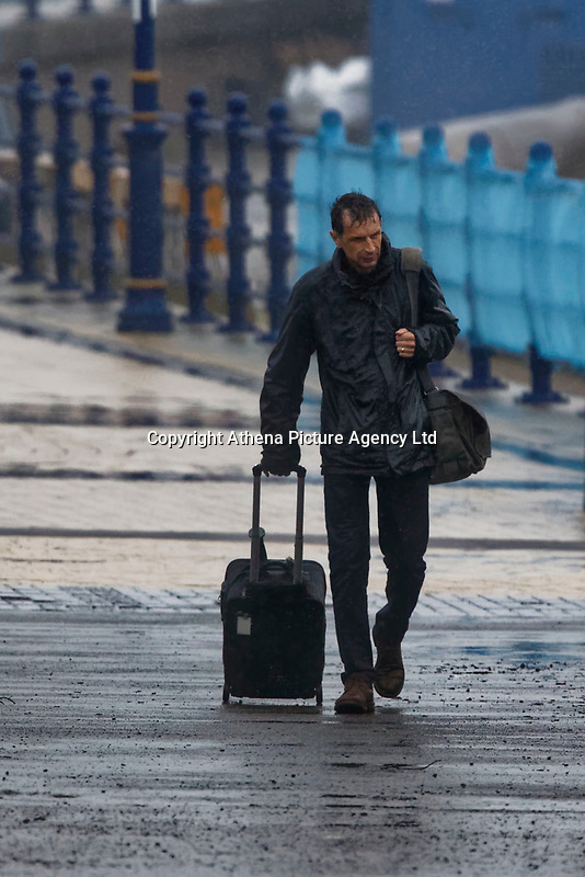 Pictured: A man walks in the rain by the promenade in Porthcawl, Wales, UK. Friday 12 October 2018<br /> Re: Strong winds and rain caused by Storm Callum in south Wales, UK.