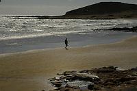 Single silhouetted figure walking along sandy beach. El Medano, Tenerife, Canary Islands, Spain.