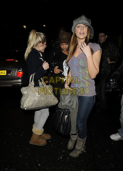 MOLLIE KING, VANESSA WHITE & UNA HEALY Of The Saturdays.At the Mayfair Hotel, London, England, UK, 16th January 2010..full length denim skinny jeans grey gray bag  cap hat t-shirt brown bag back coat side suede boots balenciaga uggs ugg hand .CAP/CAN.©Can Nguyen/Capital Pictures