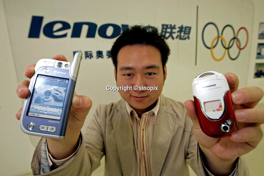 Jacky Yuan, Branding & Communications for Lenovo Computer, shows two models of mobile phones in the showroom of Lenovo Computers Beijing headquarters. On left is the PDA style and on right is the perfume scented model..