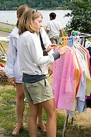Women age 22 shopping at clothing stand. Dragon Festival Lake Phalen Park St Paul Minnesota USA