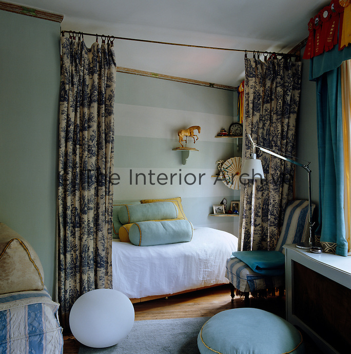 A pair of toile de Jouy curtains separates the sleeping area from the rest of the bedroom