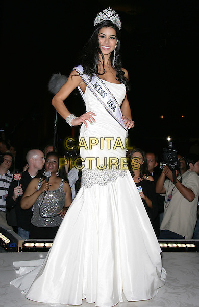 RIMA FAKIH.2010 Miss USA Pageant at the Planet Hollywood Resort Hotel and Casino, Las Vegas, Nevada, USA..May 16th, 2010.full length white dress gown fishtail sash silver hands on hips.CAP/ADM/MJT.© MJT/AdMedia/Capital Pictures.