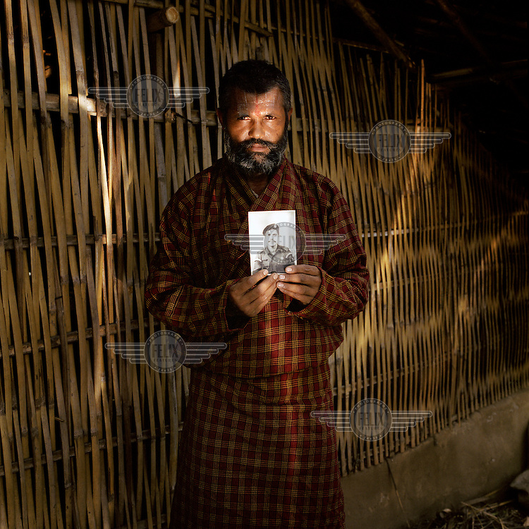 48-year-old Kadhananda Luitel, a Bhutanese refugee, standing in the reflected light from a solar cooker. Kadhananda, who is pictured with the only objects that he took with him upon leaving his homeland, is holding a photograph of himself in his Bhutanese army dress. Like most of the first generation Bhutanese refugees, Kadhananda arrived in Beldangi camp in the early 1990s.