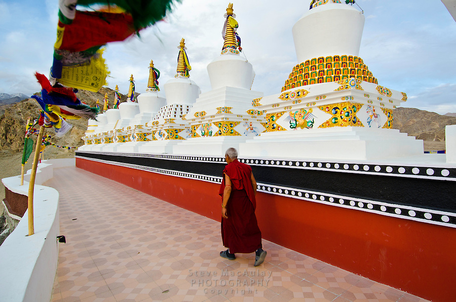 Buddhist monk circling the chortens with his prayer beads at the Thiksey Gompa in Leh, Ladakh, India